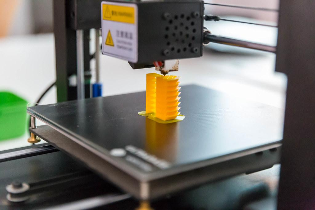 A 3D printer printing a small yellow cylinder