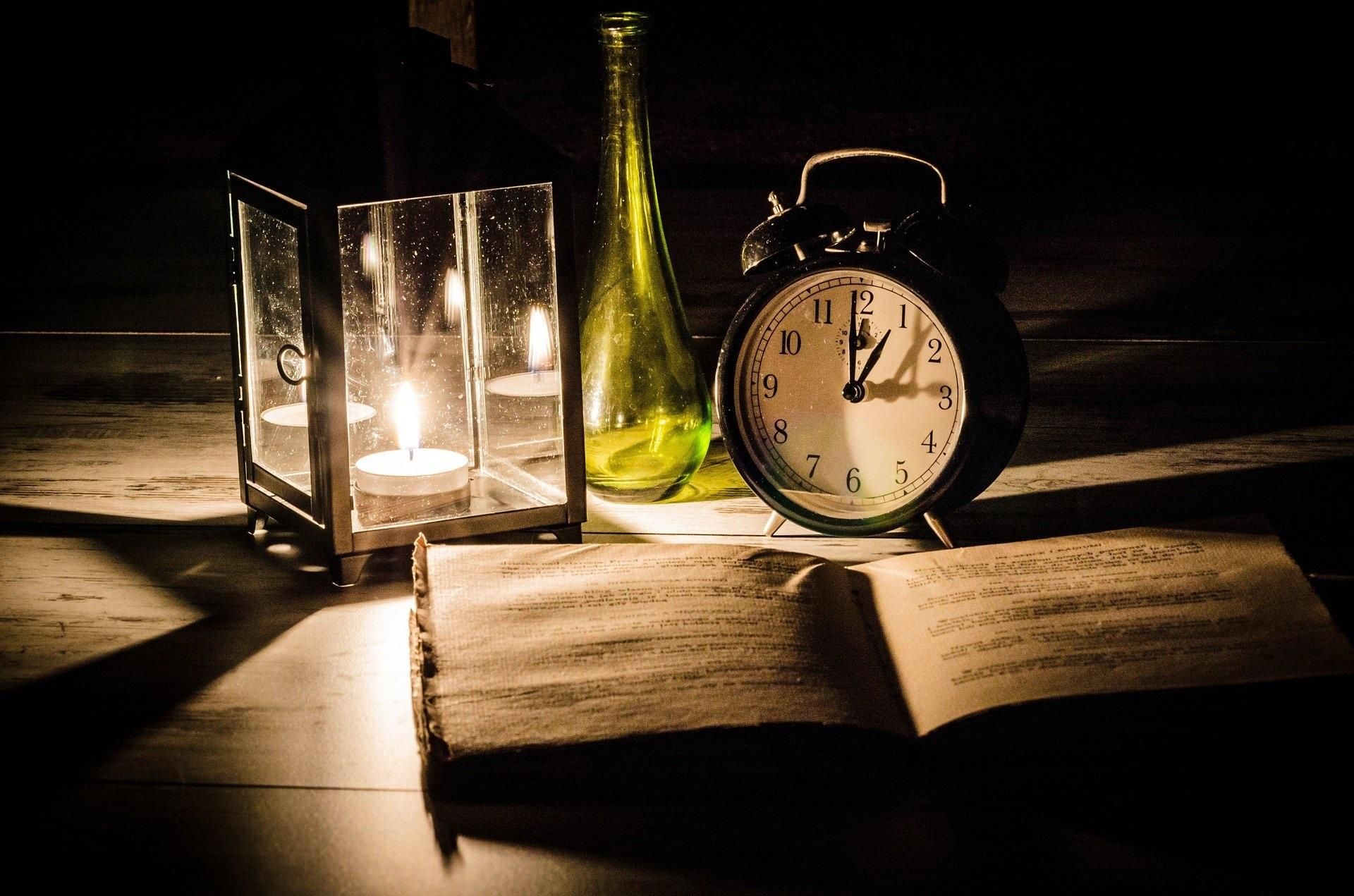 Old fashioned alarm clock and lit glass lantern behind a open book
