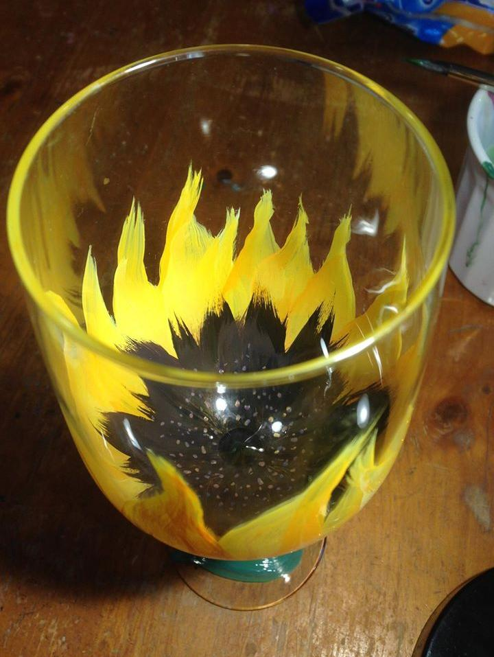 Wine glass from above with a yellow flower painted at the bottom