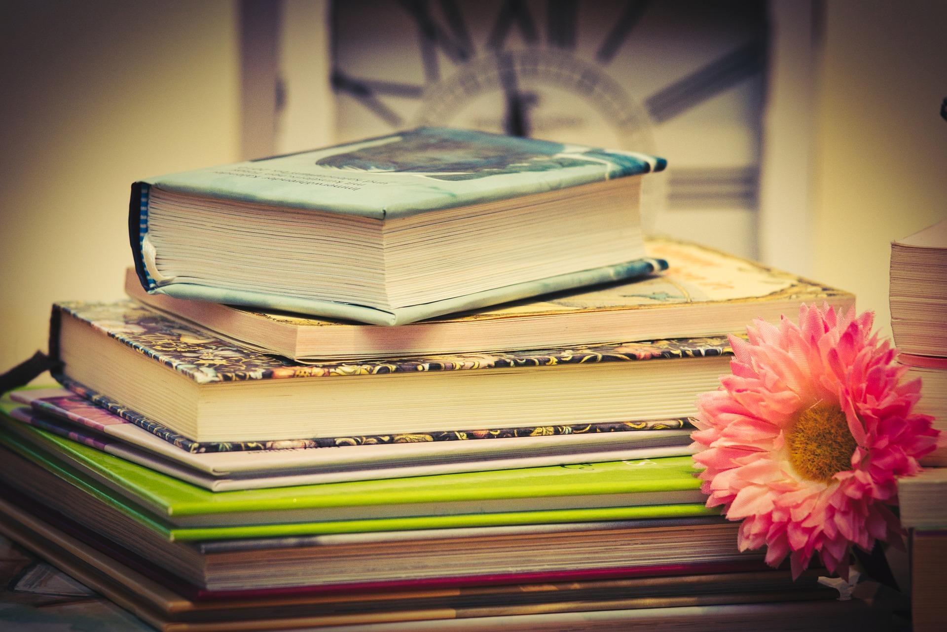 Stack of book with flower next to them