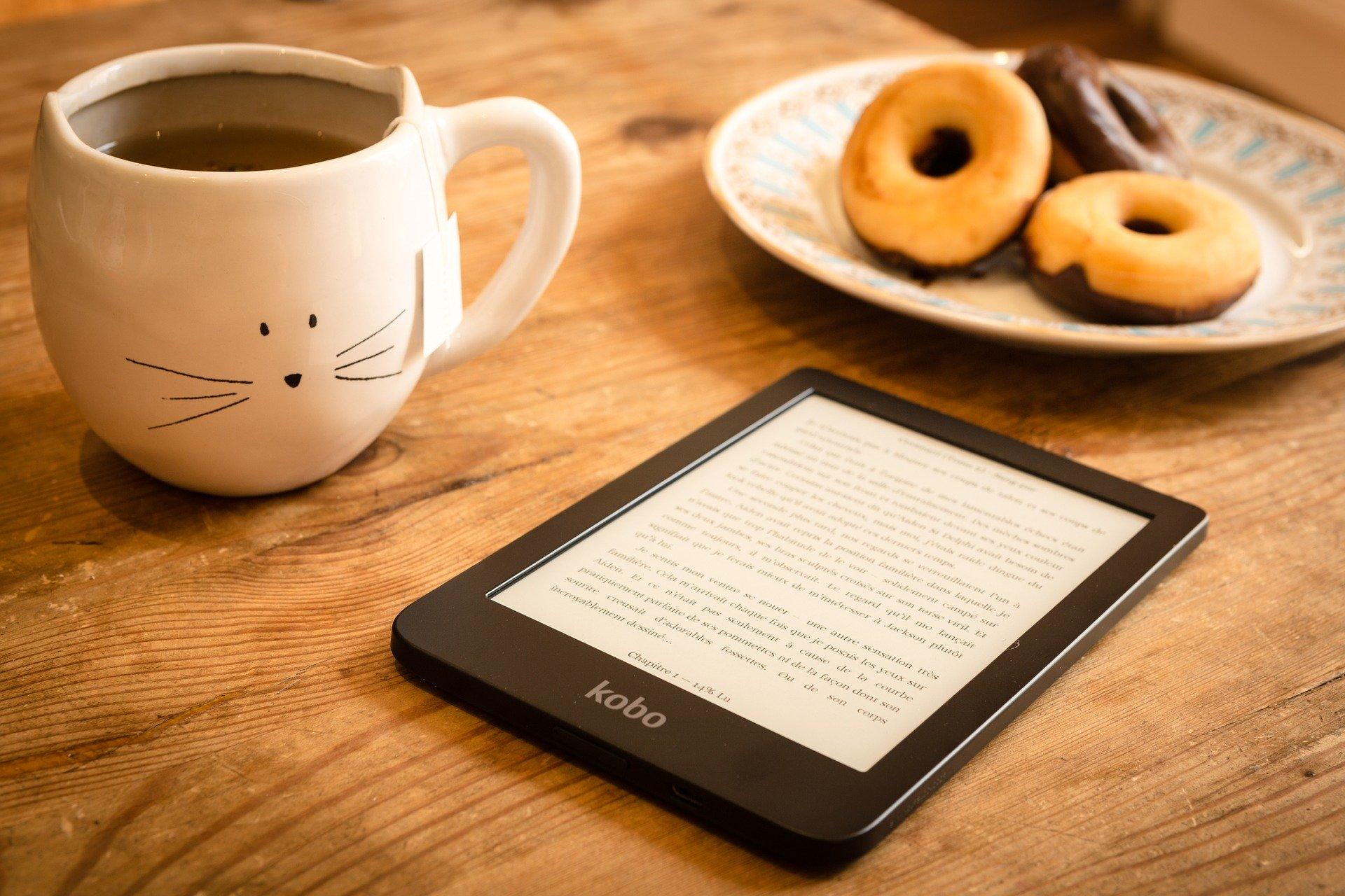 ereader sitting on table with cat mug with tea and donuts