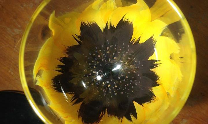 shot from above a wineglass with a yellow flower painted around the base